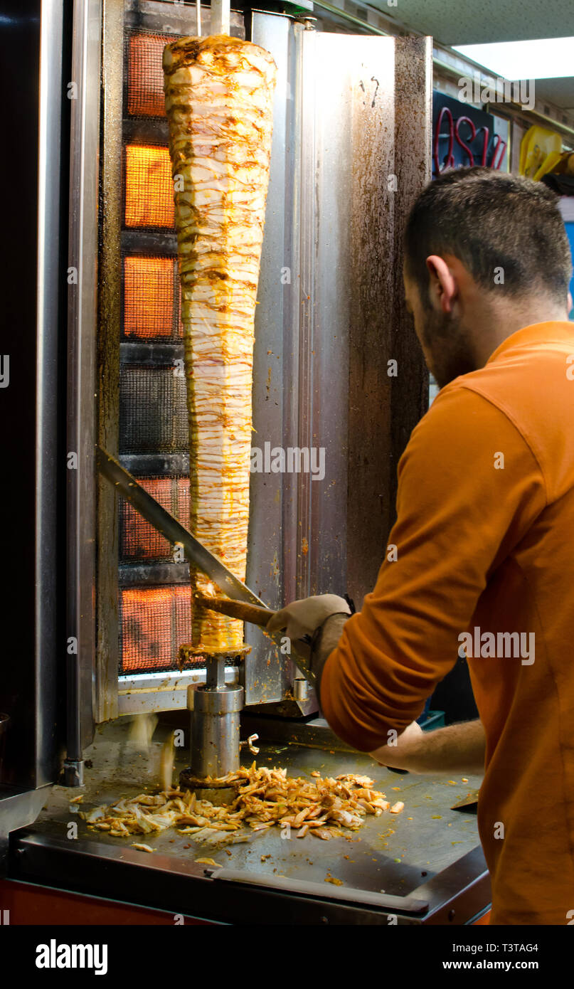 Istanbul, Turkey, March 08, 2019:  worker at fast food restaurant cutting doner kebab on rotating vertical spit, traditional street food, night shot - Stock Image