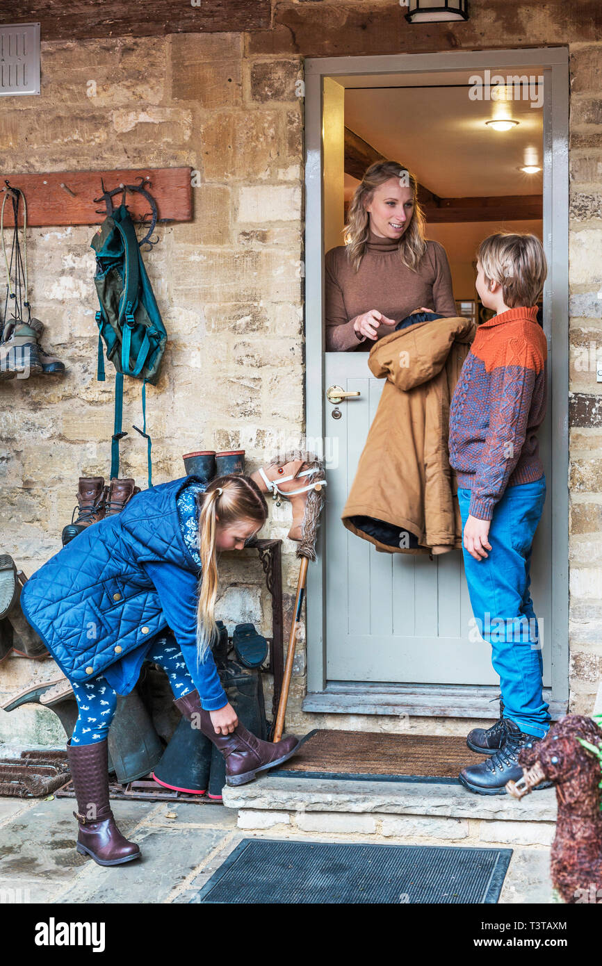 Mother standing in french-door doorway with son and daughter - Stock Image
