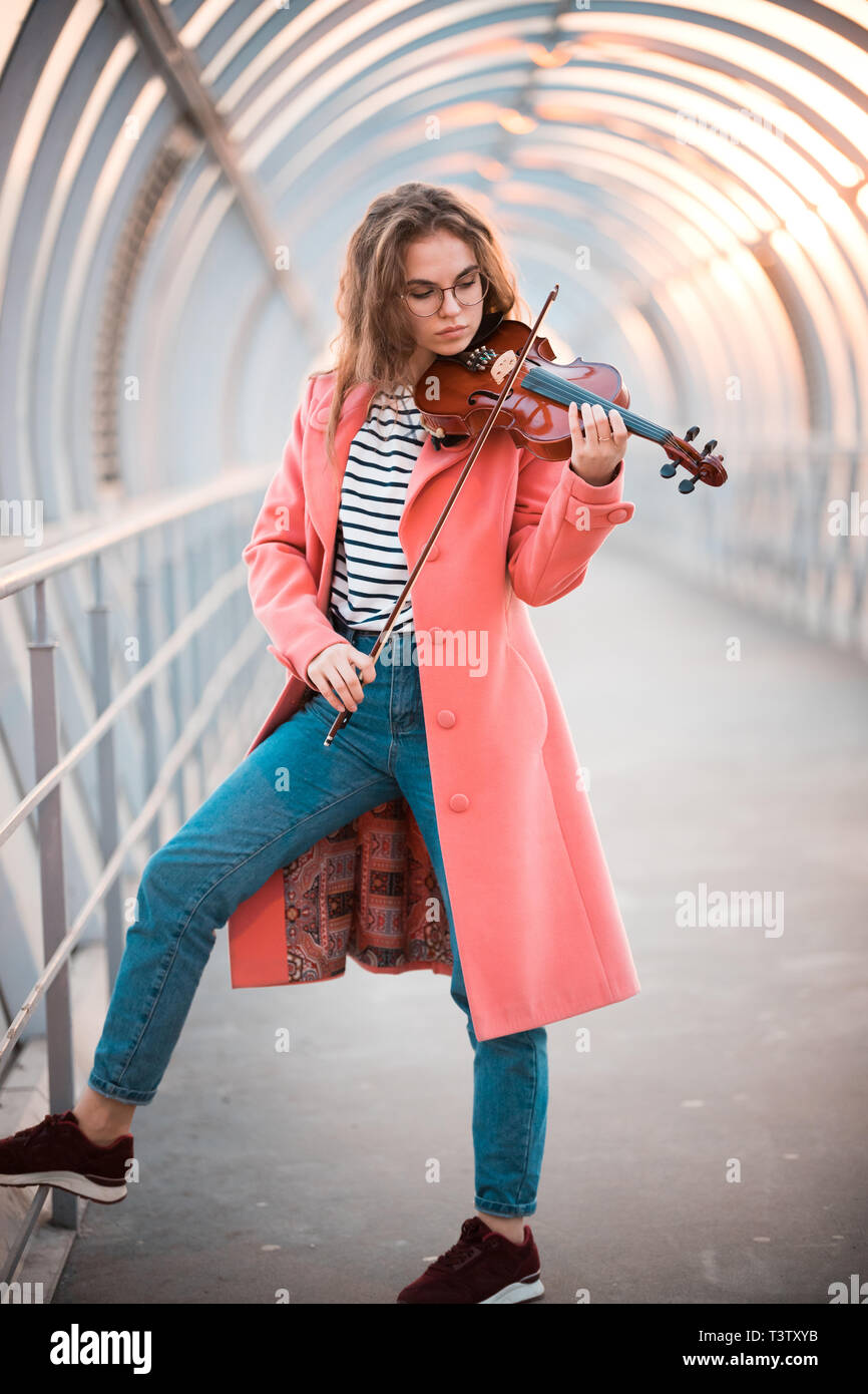 Young woman in pink coat standing on the overhead passage playing violin - Stock Image