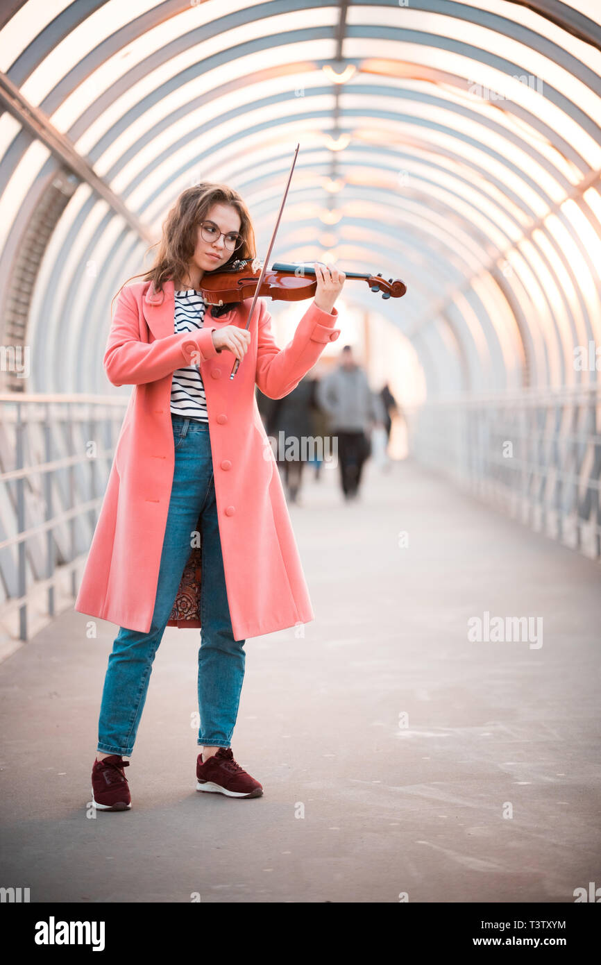 Inspired young woman in pink coat playing a fiddle on the overhead passage - Stock Image