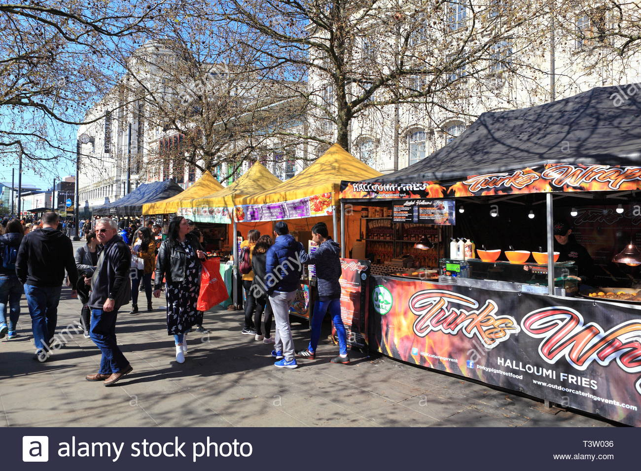 Outdoor food market stalls with public around in view at Manchester UK - Stock Image
