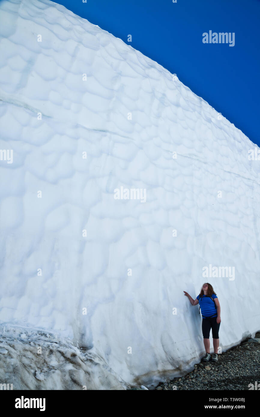 Young woman standing beside a giant snow bank in Whistler, British Columbia, Canada - Stock Image