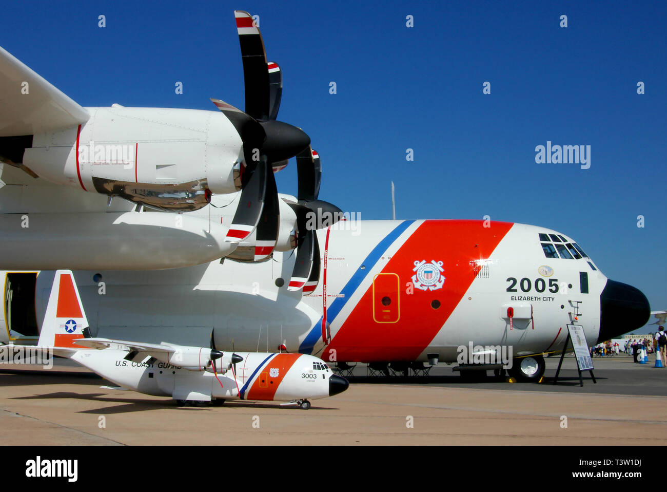 United States Coast Guard Lockheed HC-130J Hercules transport plane with similar model plane on display at RAF Fairford airshow. Space for copy - Stock Image