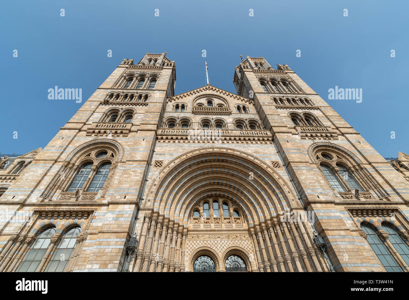 A wide view of the front of the Natural History Museum in London on a bright day - Stock Image
