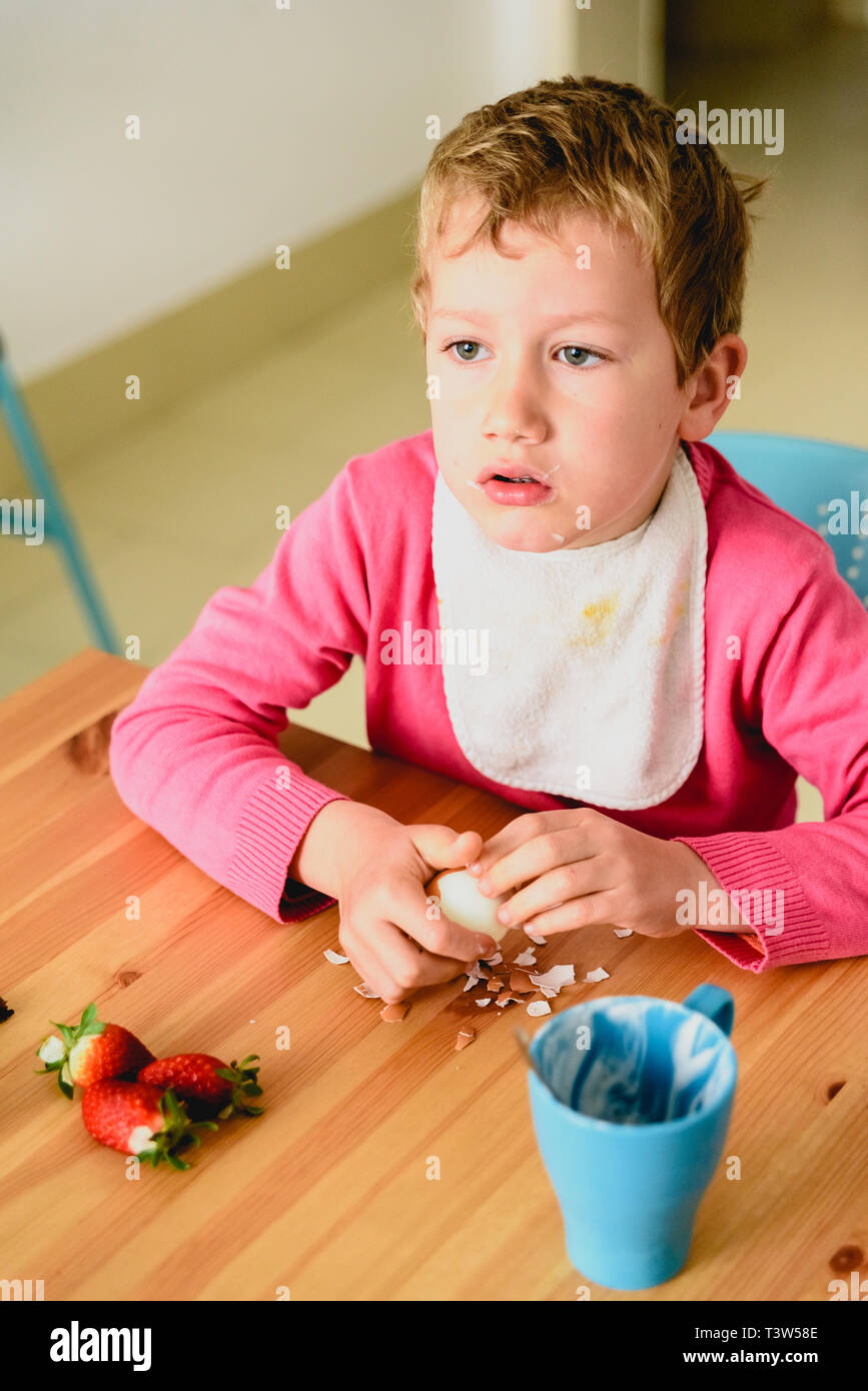 Gawking boy watching television during the meal. - Stock Image