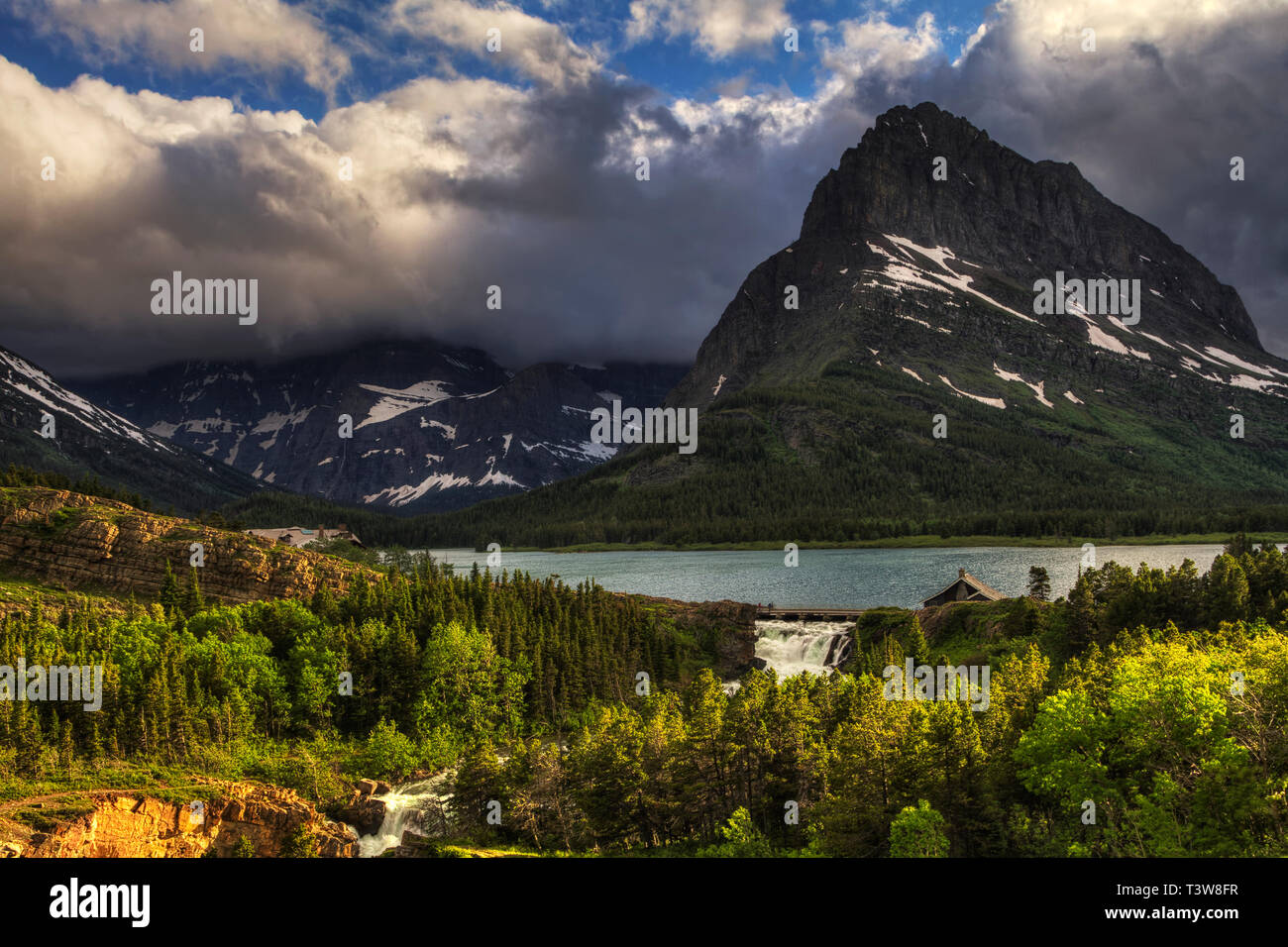 In Glacier National Park, the weather can be unpredictable. One minute it might be clear, the next wind, storm clouds and rain or snow. The one thing  - Stock Image
