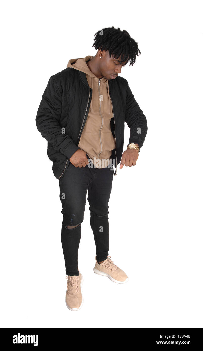 A full body image of an African American man standing in a black  jacket and jeans, looking at his watch, isolated for white background - Stock Image