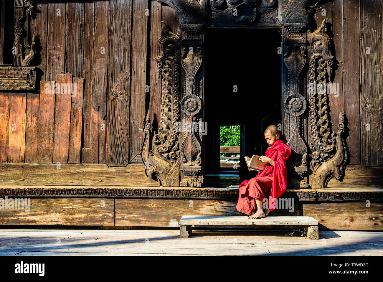 Asian monk reading by ornate doorway to temple - Stock Image