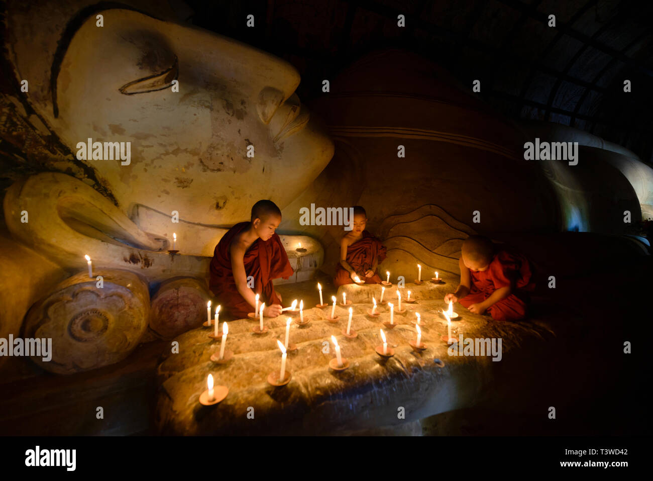 Asian monks lighting candles in temple - Stock Image