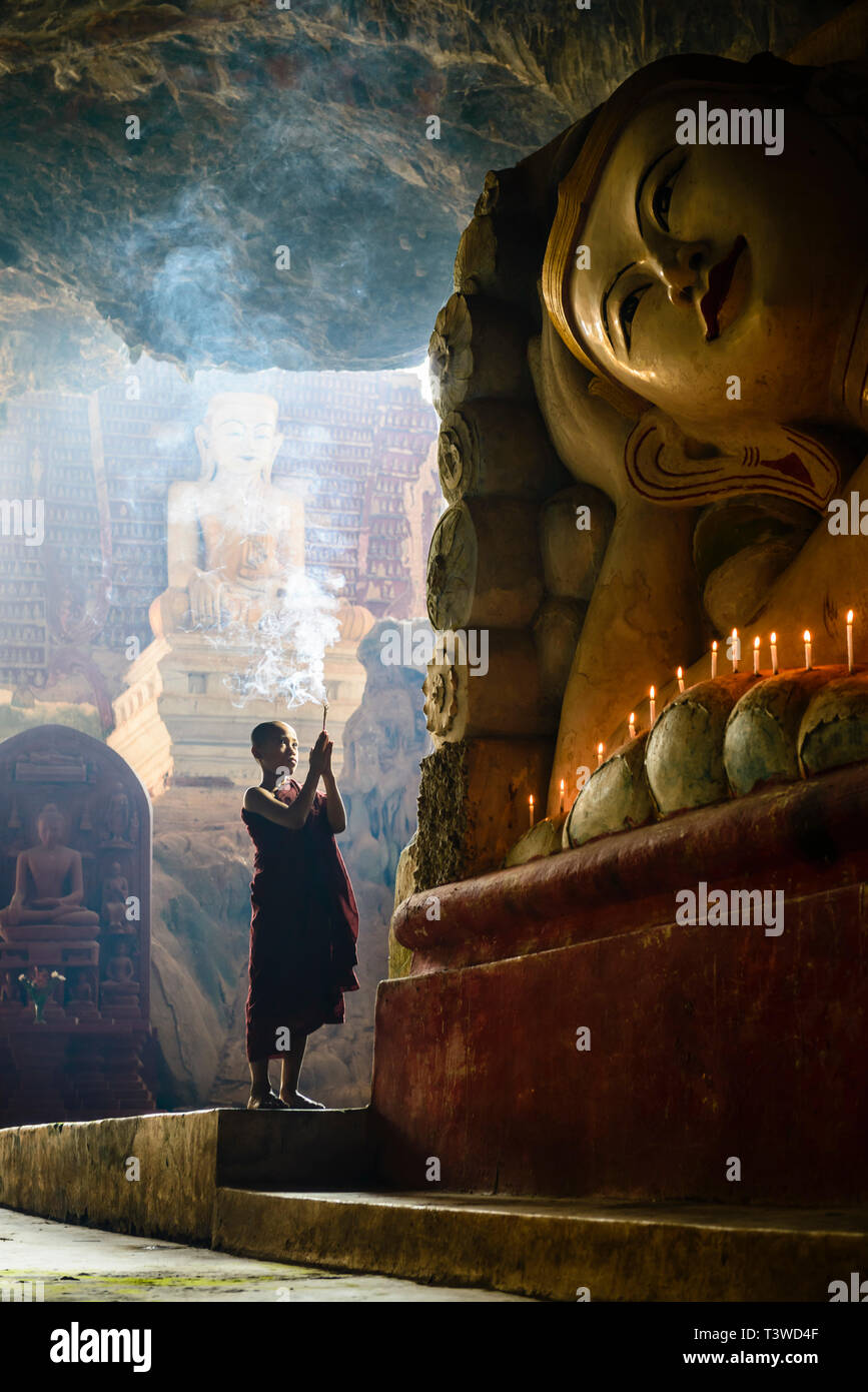 Asian monk lighting incense in temple - Stock Image