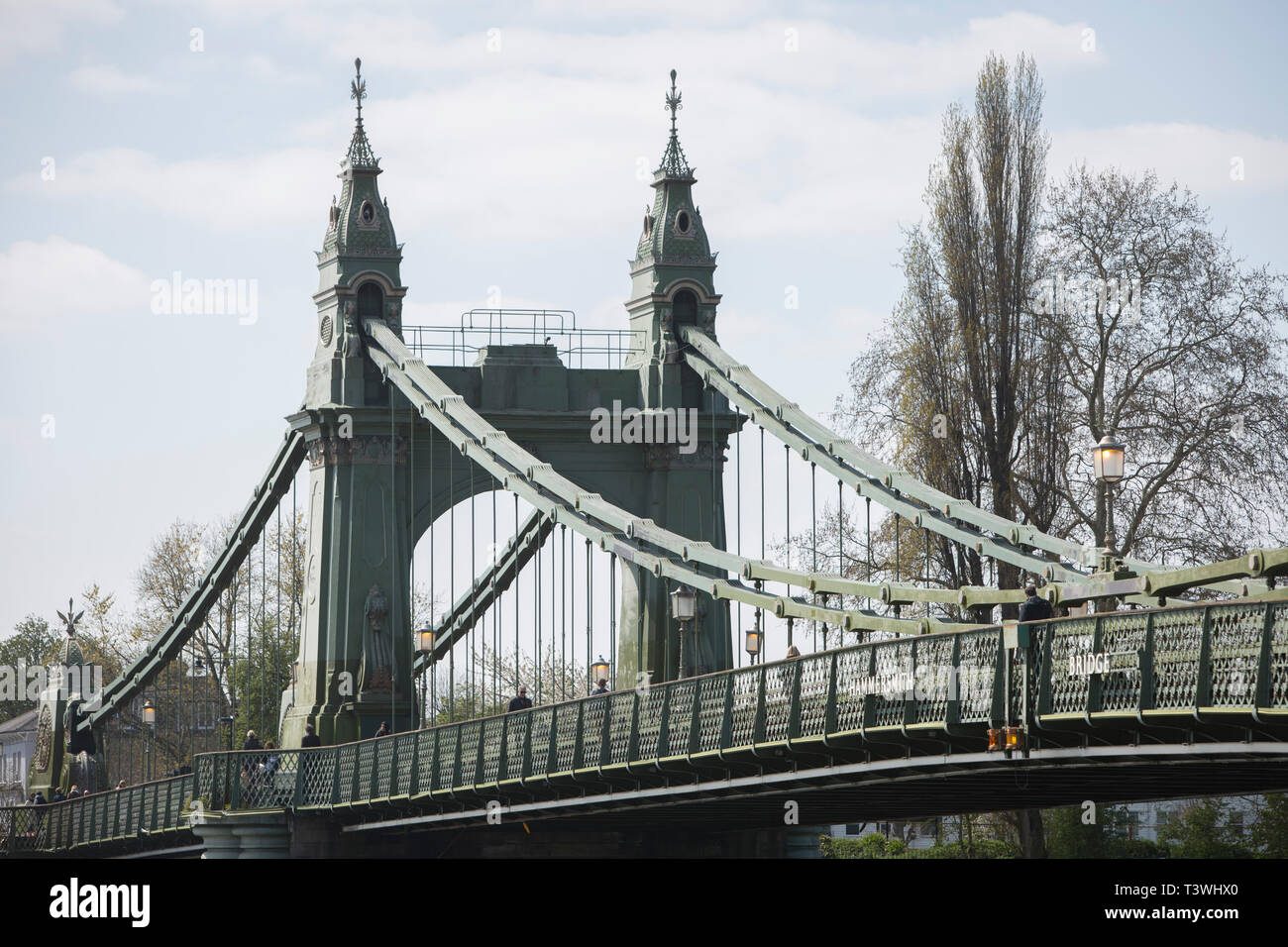 After being closed indefinitely to all traffic due to structural faults, pedestrians walk across Hammersmith Bridge, on 11th April 2019, in west London, England. Safety checks revealed 'critical faults' and Hammersmith and Fulham Council has said it's ben left with no choice but to shut the bridge until refurbishment costs could be met. The government has said that between 2015 and 2021 its is providing £11bn of support to the 132-year-old bridge. - Stock Image