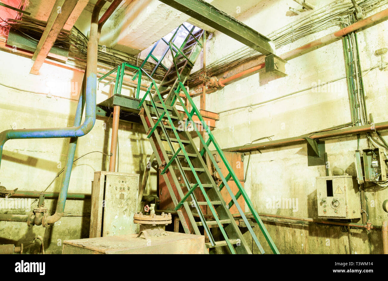 A flight of stairs from the basement of the pumping station. Basement of a water pumping station. Abandoned post-apocalyptic view of the basement pump - Stock Image