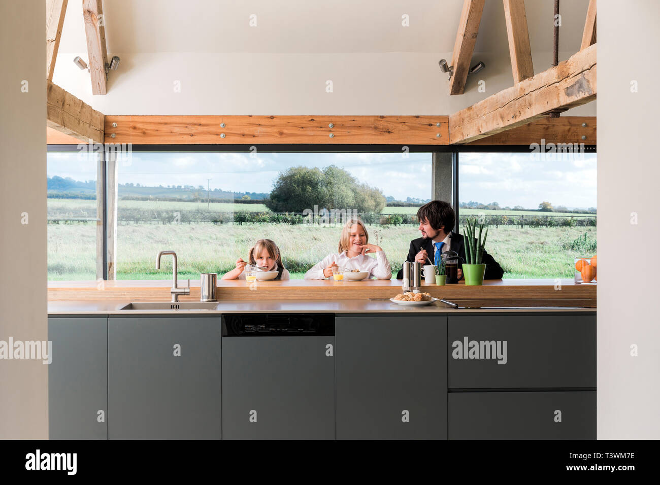 Caucasian father and children eating breakfast in kitchen - Stock Image
