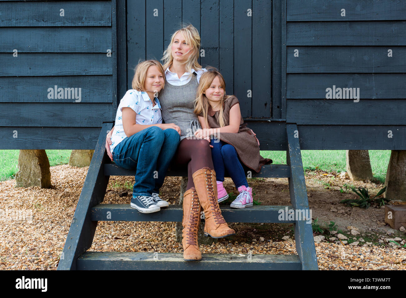 Caucasian mother and children hugging at shed - Stock Image