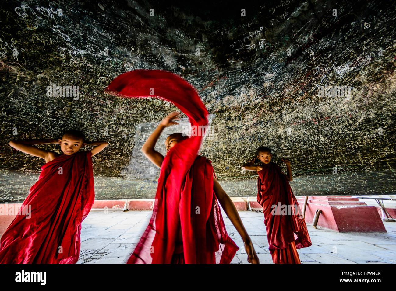 Asian monks dancing in historic temple, Mingun, Mandalay, Myanmar - Stock Image