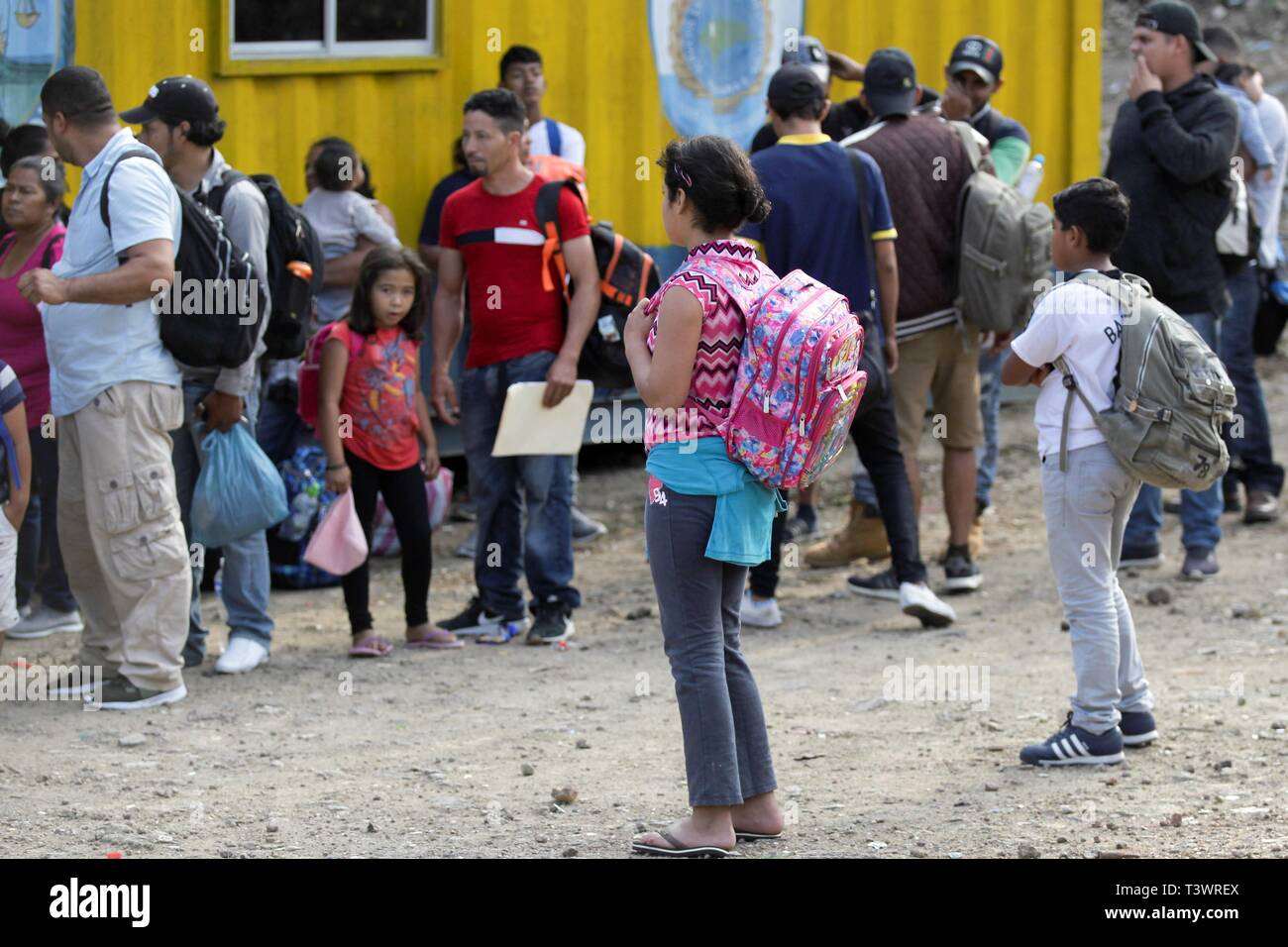 Dozens of Hondurans wait at a police checkpoint to verify if