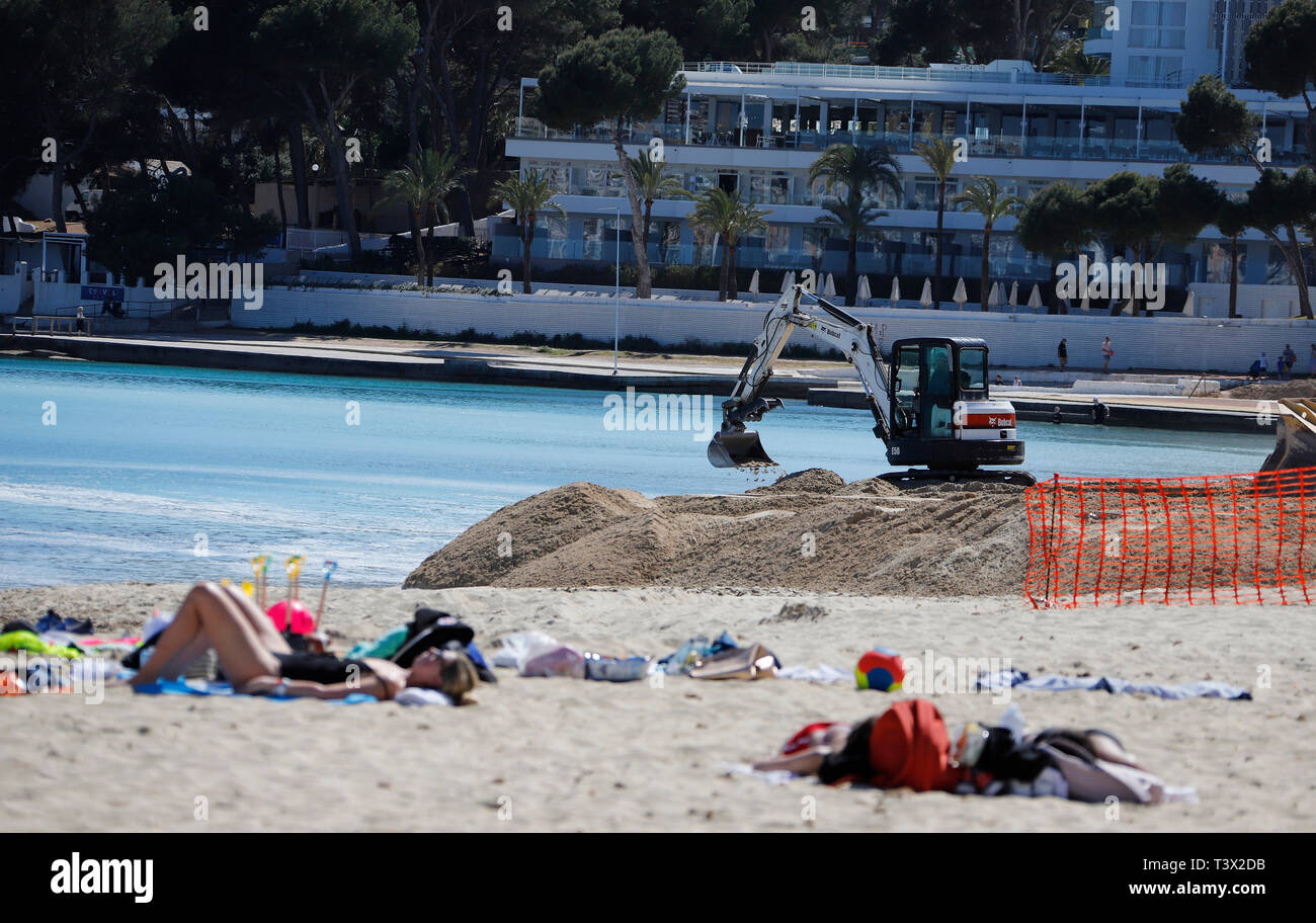 11 April 2019, Spain, Calvia: Construction machinery and tourists