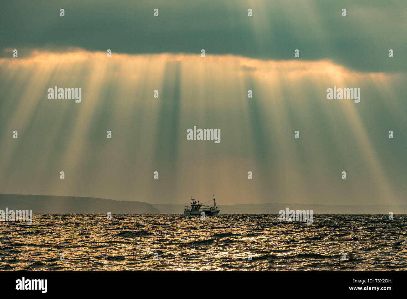 Mousehole, Cornwall, UK. 12th Apr, 2019. UK Weather. The sun made brief appearance though the clouds this morning, bringing some spectular crespicular rays over the sea at Mounts Bay Credit: Simon Maycock/Alamy Live News Stock Photo