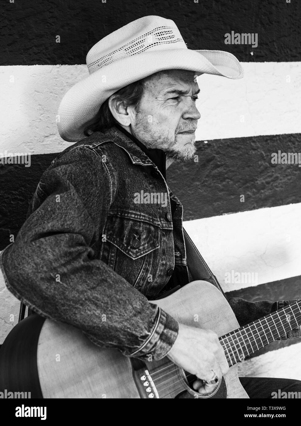 8c13d694370 Old cowboy with cowboy hat and gray beard plays a guitar while standing  next to a