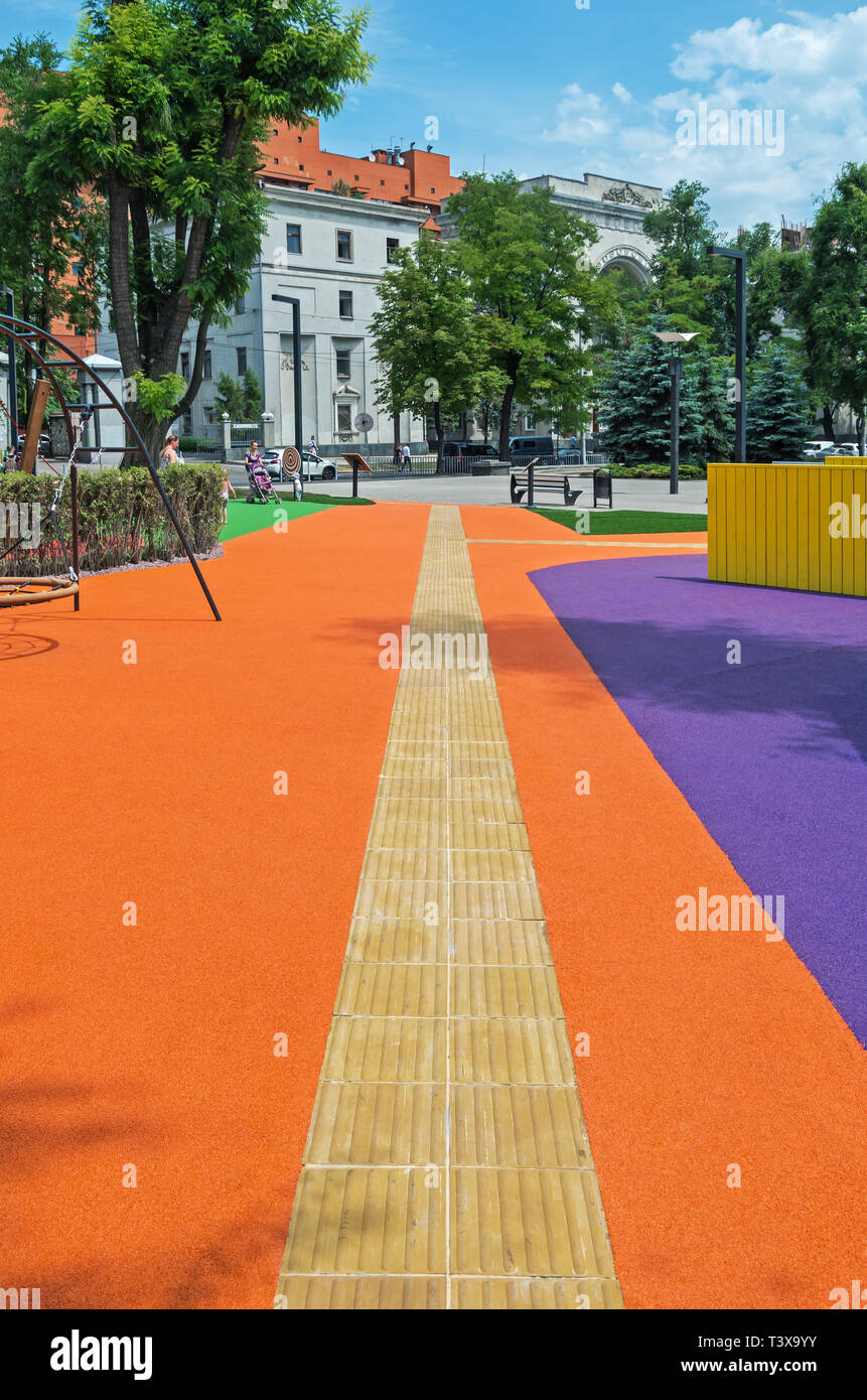 Dnipro, Ukraine - June 27, 2018: Pathway of tactile tiles for blind and visually impaired people in an inclusive city park - Stock Image