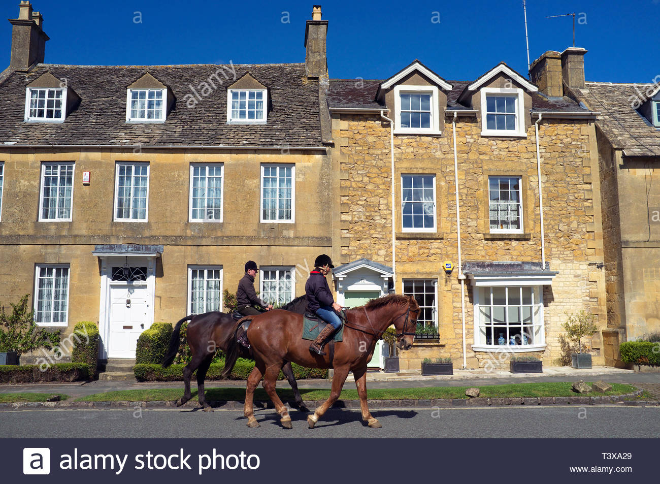 Horse riders trot by in the Cotswold village of Broadway in Worcestershire, UK. Stock Photo