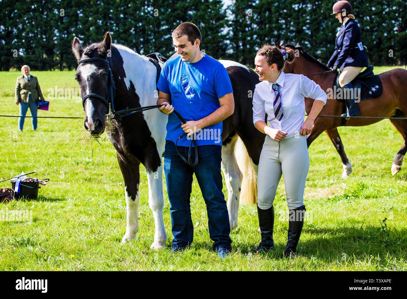 Male and female with horse at a horse show. Man holds the horse while the woman prepares to ride. Stock Photo