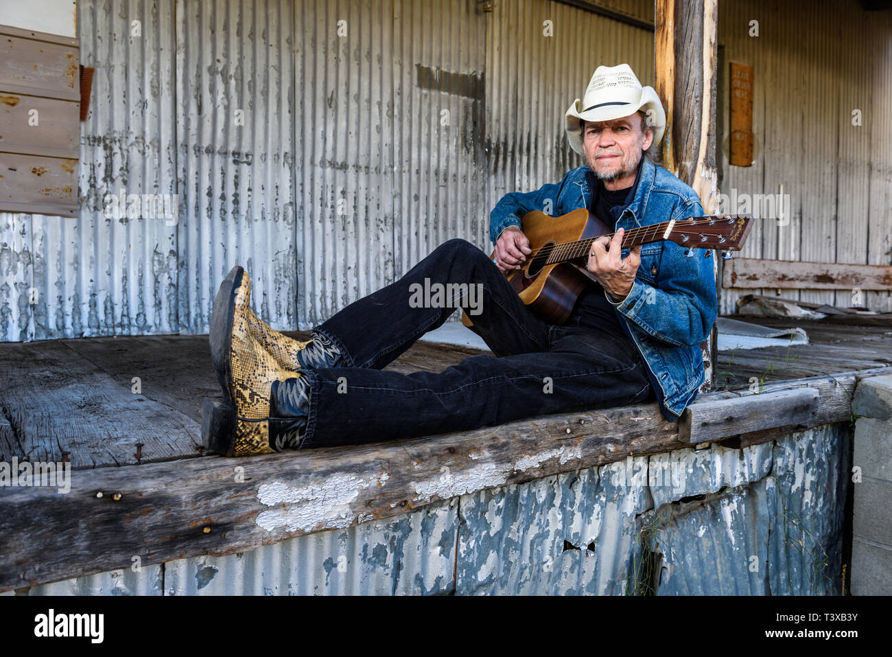 9a271e22b0c26 Old Cowboy wears cowboy hat and boots plays a guitar while sitting on an old  dock