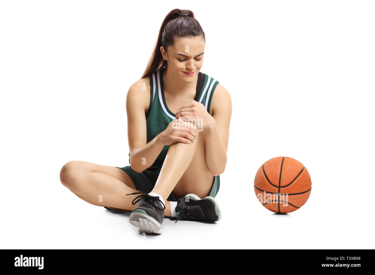 Young female basketball player sitting on a floor and holding her painful knee isolated on white background - Stock Image