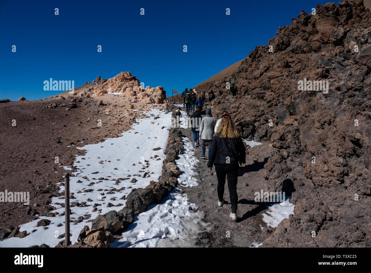 Rear view of tourists hiking on top of Teide volcano - Stock Image