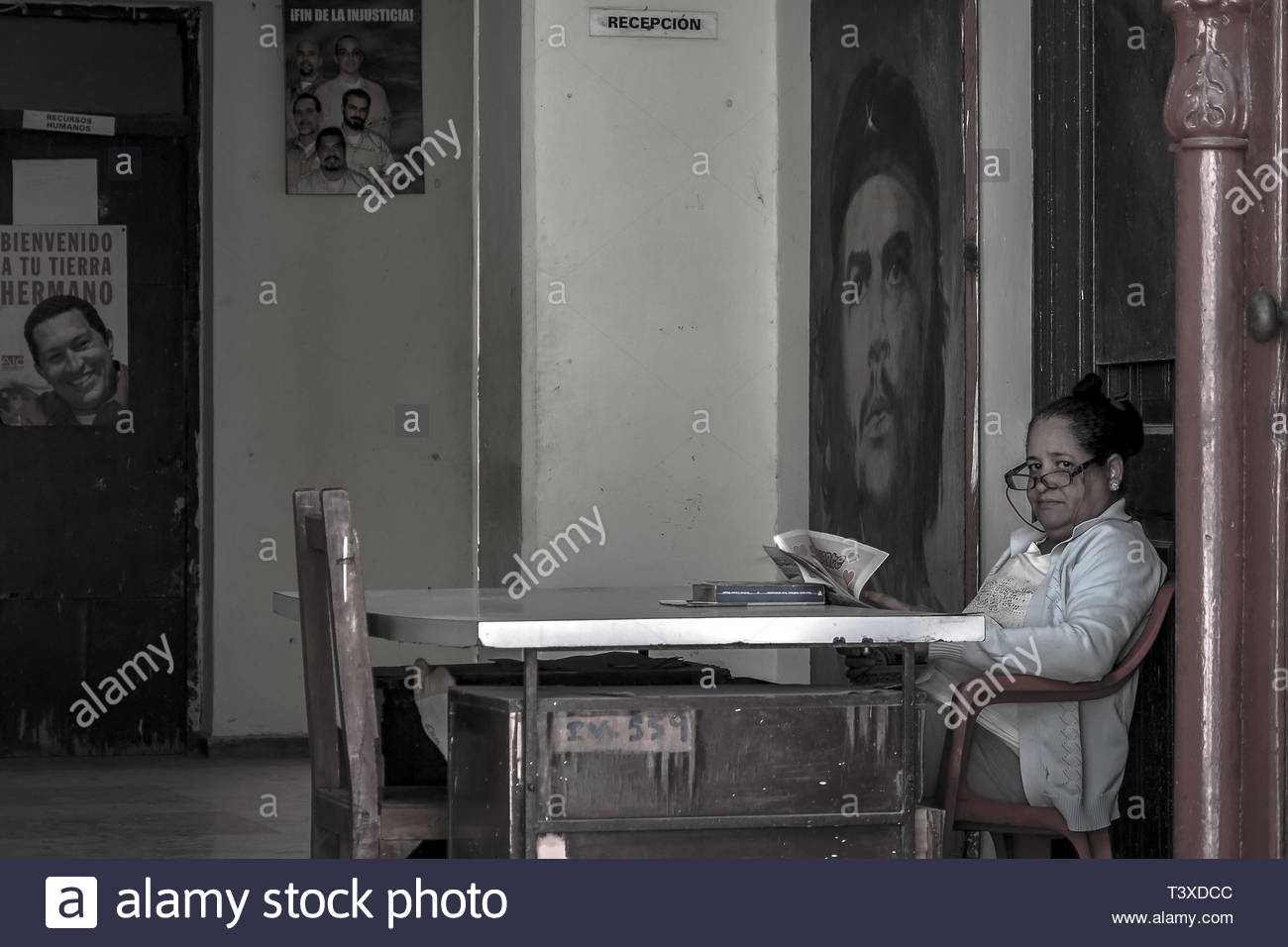 March, 2016 - Havana, Cuba: A state employee reads the newspaper at the reception of a Defense Committee of the Revolution (CDR). In the background, t - Stock Image