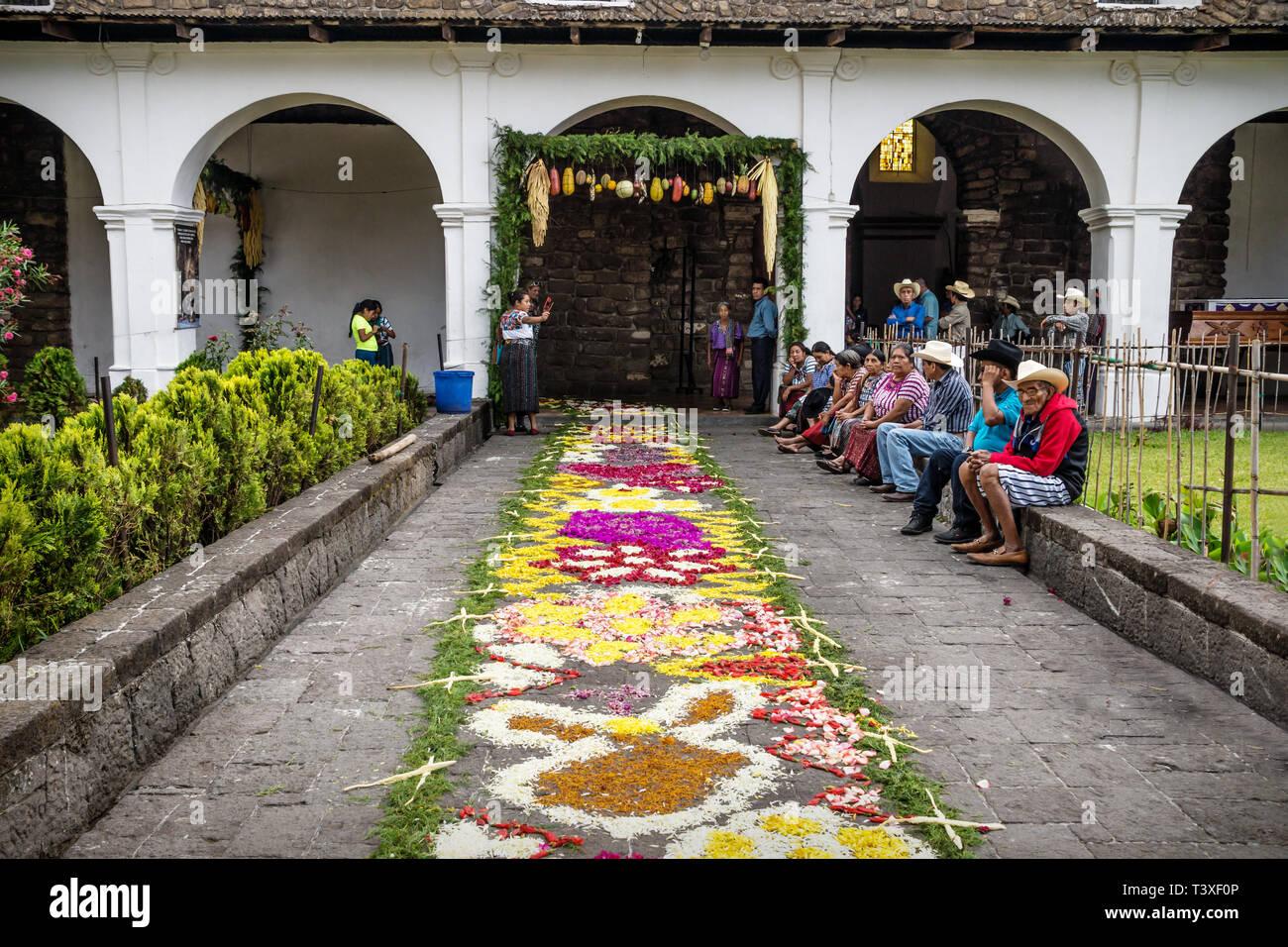 Santiago Atitlan, Guatemala - 29 March 2018: Alfombre, flower carpet for Semana Santa in church backyard and local people sitting along - Stock Image
