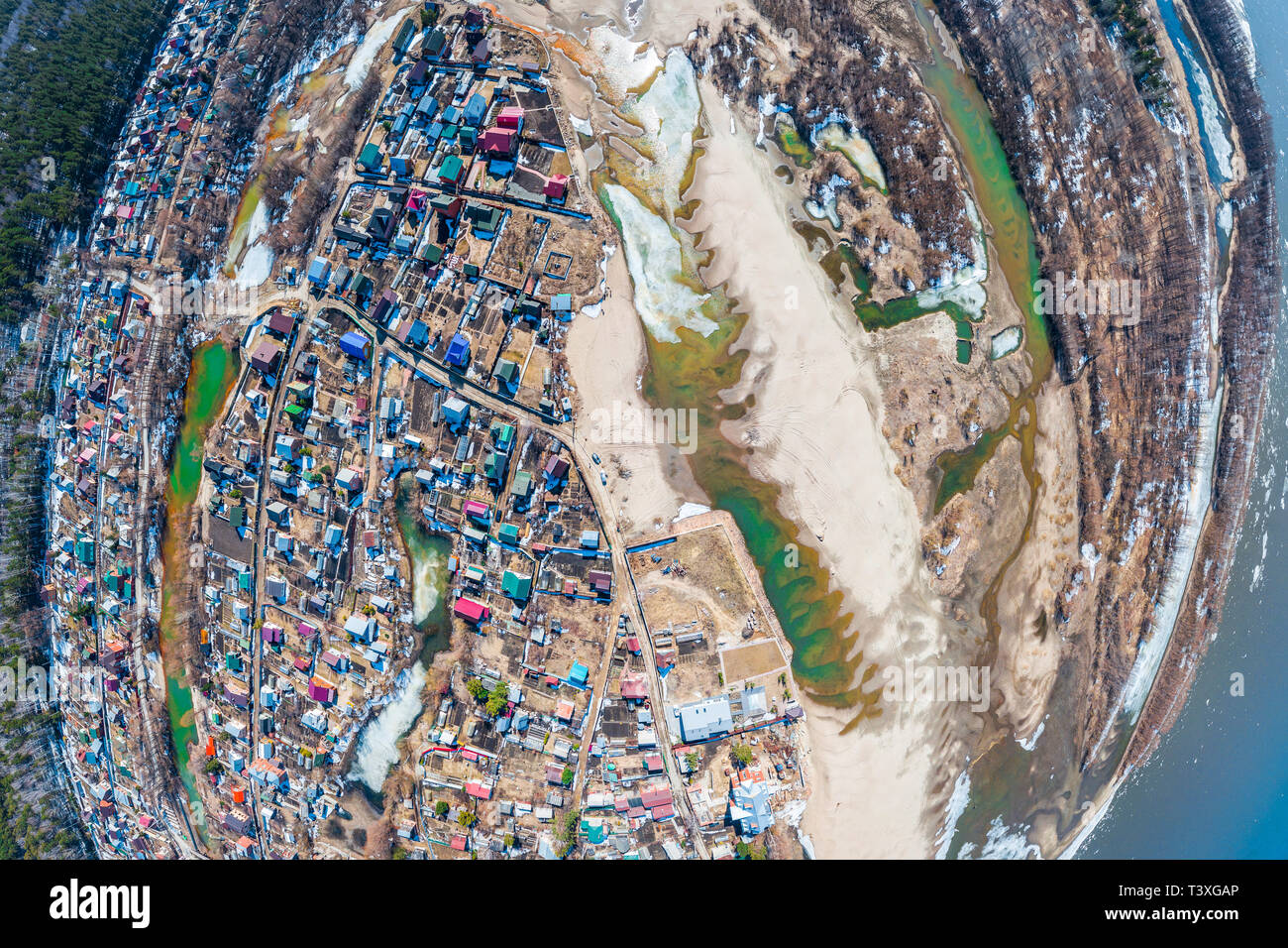 Helicopter drone shot. Aerial photography of a small village with villas and cottages, river, beach,forest and roads. Panoramic city 360  shot from ab - Stock Image