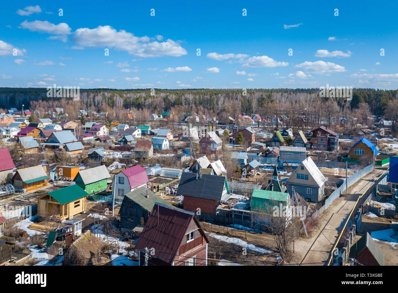 Aerial photography of a a cottage village with colorful houses, road, green trees and yards. Helicopter drone shot - Stock Image