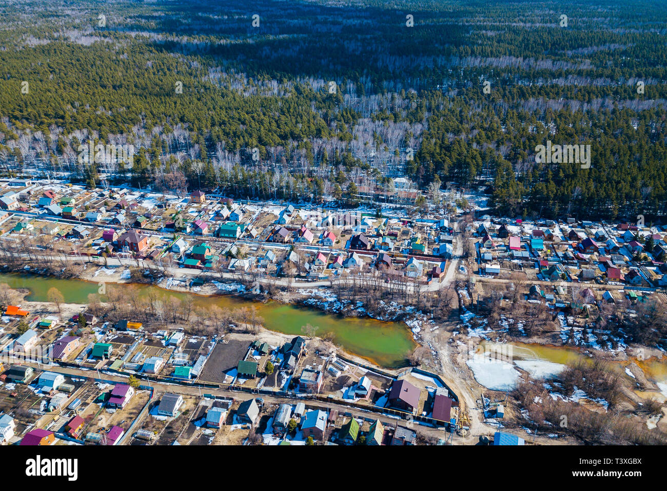 Aerial drone view of an old traditiona village in the forest, on background bly sky. - Stock Image