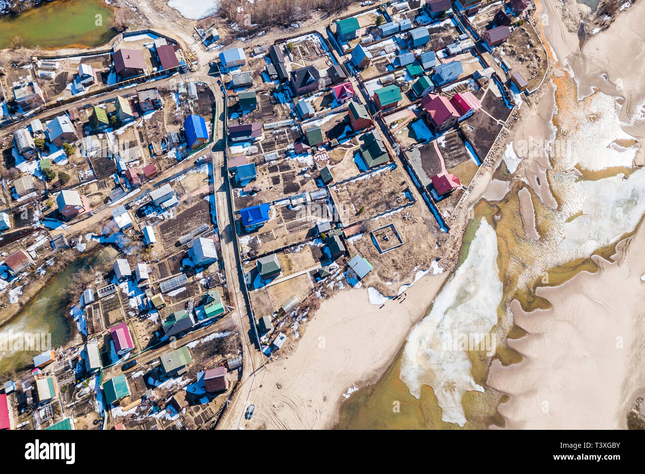 Aerial photography of a small village with villas and cottages, river, beach,forest and roads. Helicopter drone shot - Stock Image