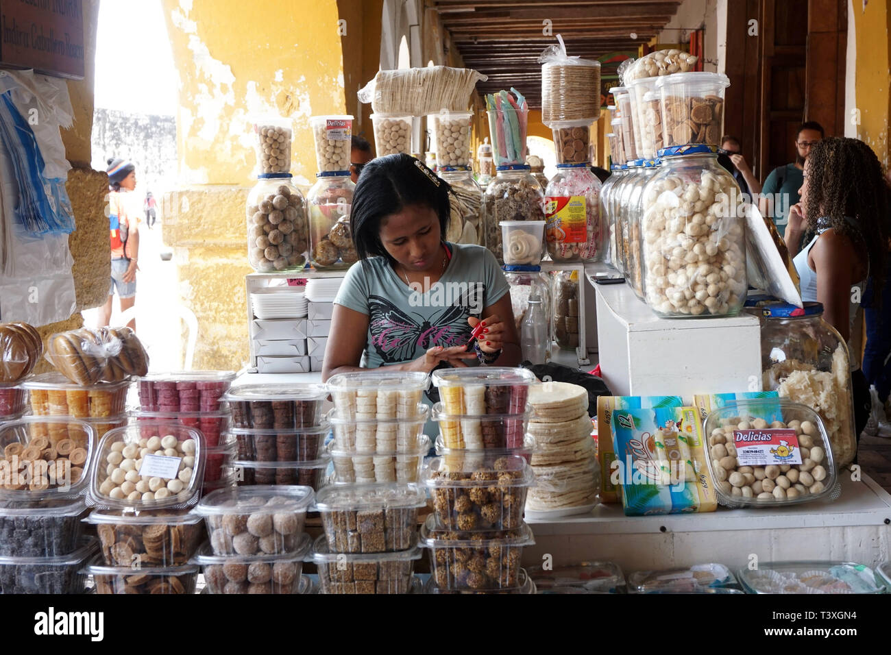 Young Female Stall Holder surrounded by Sweet Treats and engrossed in painting her Nails - Stock Image
