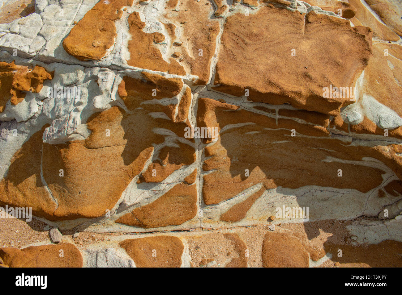 A limestone rock outcrop with different bands of rock, color and patterns - Stock Image