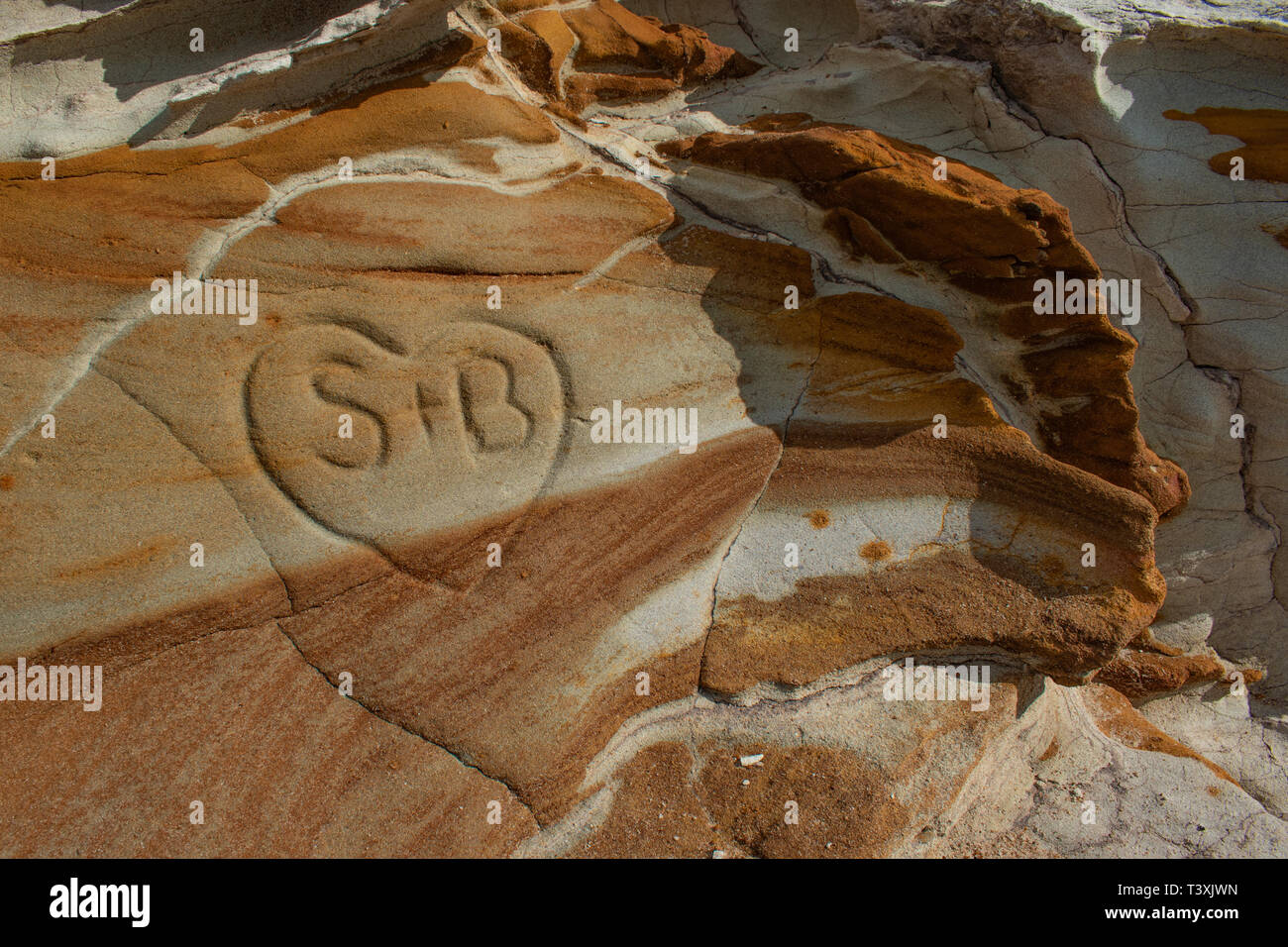A heart carved into a limestone rock outcrop with different bands of rock, color and patterns - Stock Image