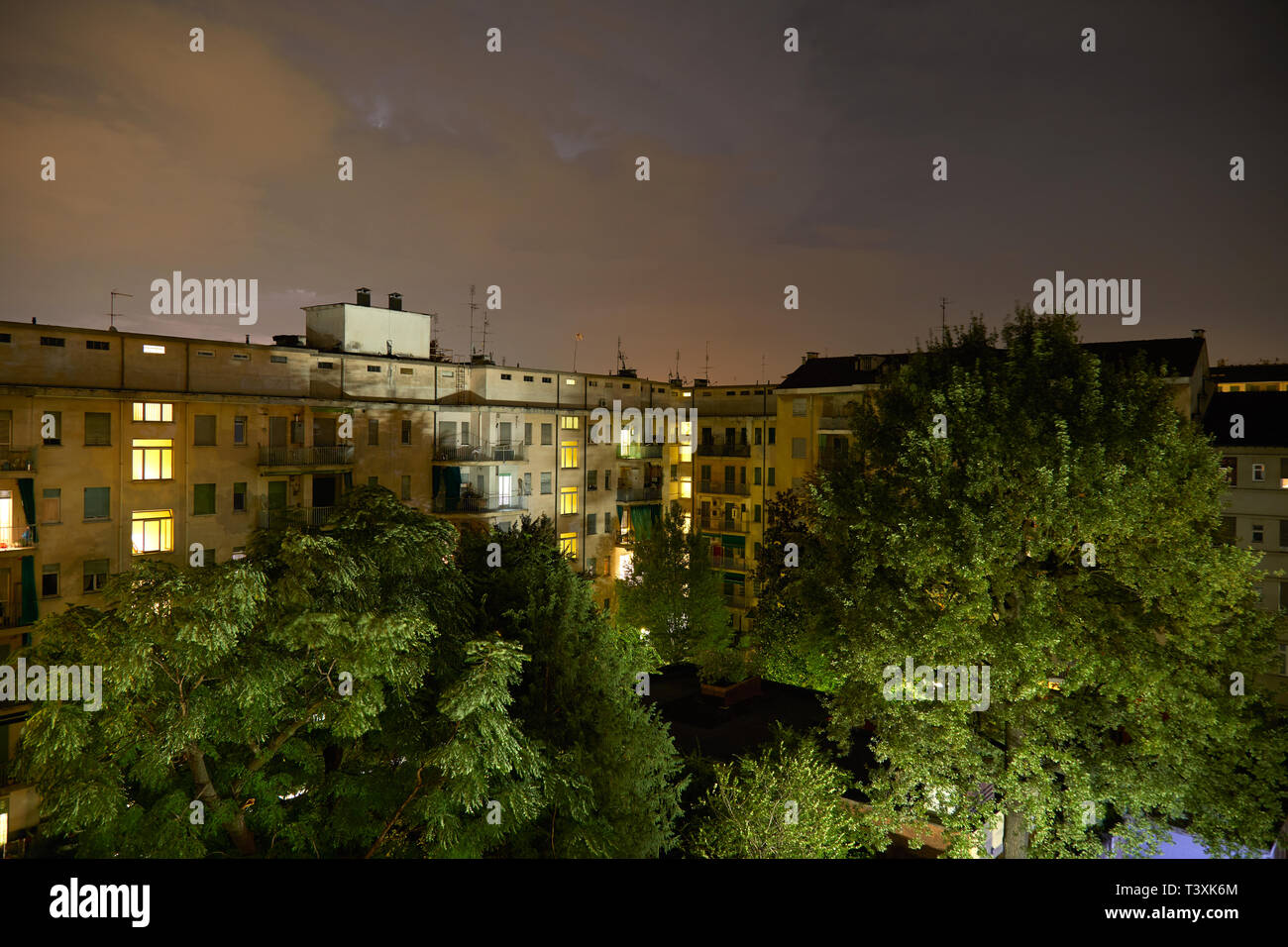 Buildings and green trees at night, illuminated cloudy sky Stock Photo