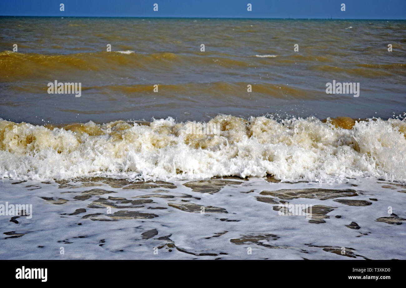 Sea view of the wave forming white sea spray and bubbles as it splashes onto the shore - Stock Image