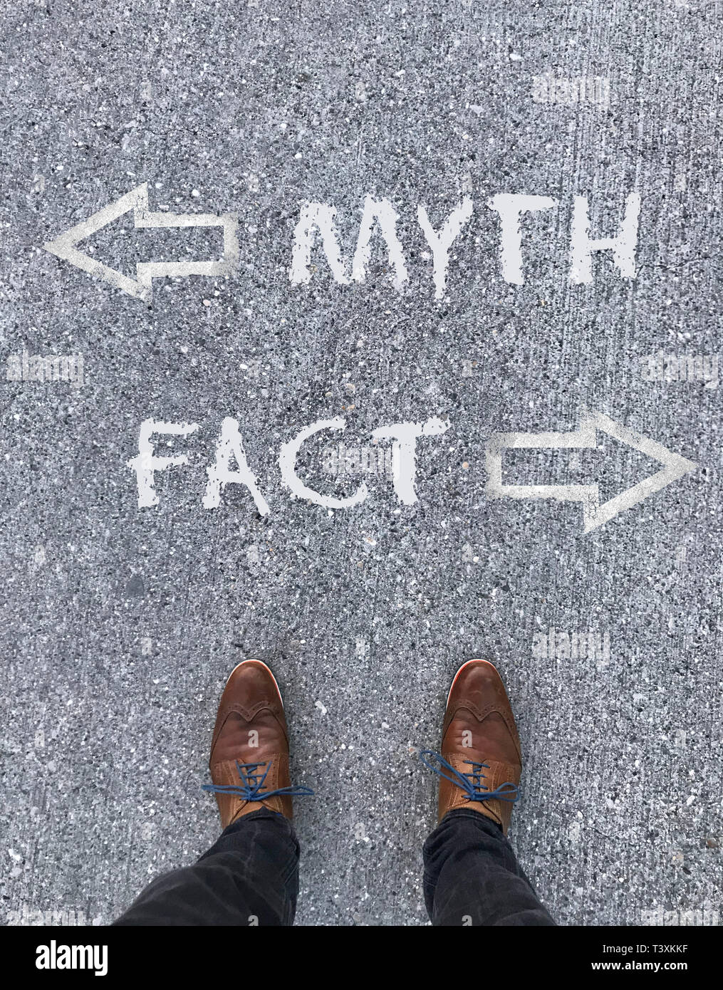 Man standing in front of two arrows and the words 'Myth' and 'Fact' - Stock Image