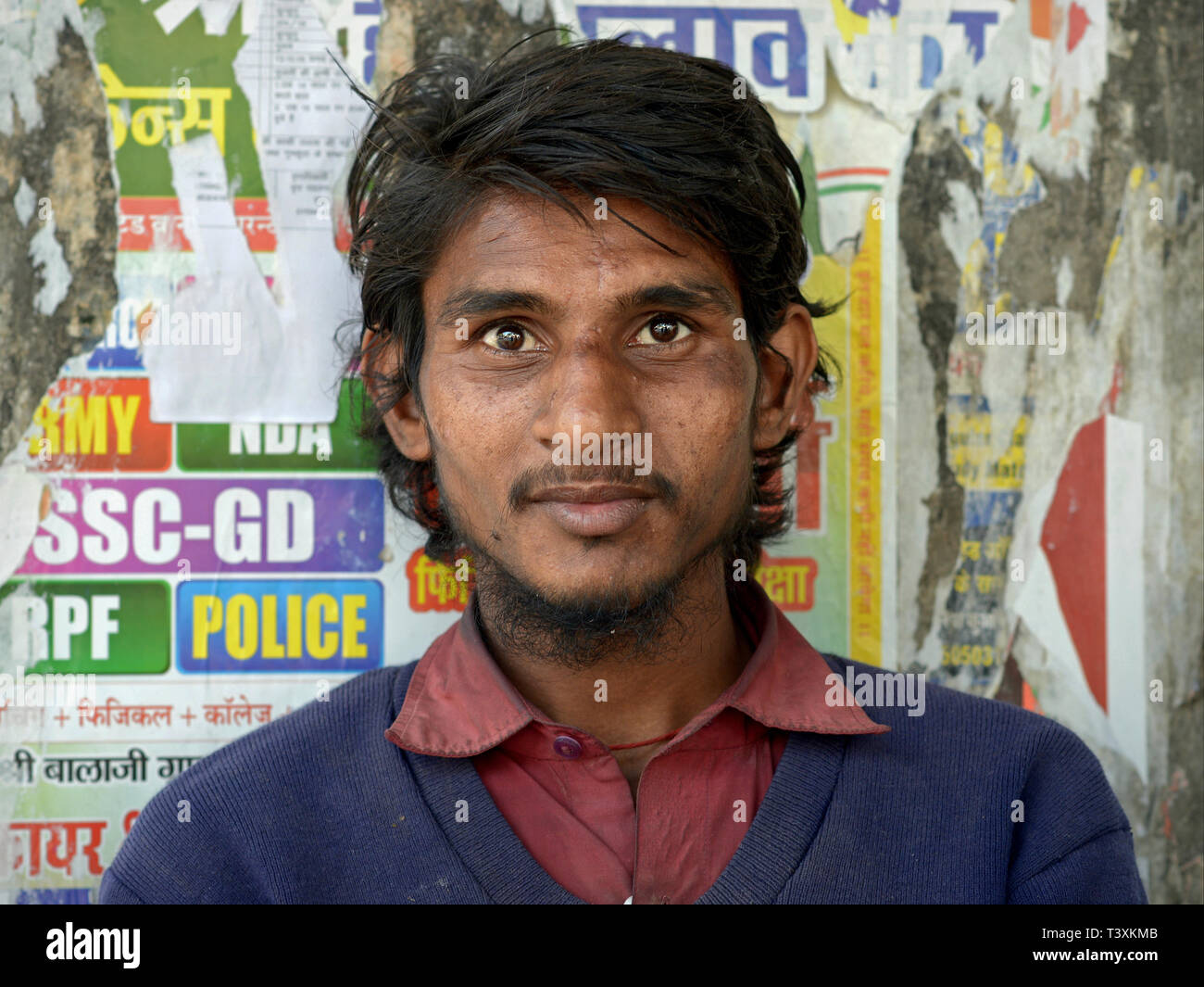 Scruffy, young Indian dalit man poses for the camera in front of a weathered poster wall. - Stock Image