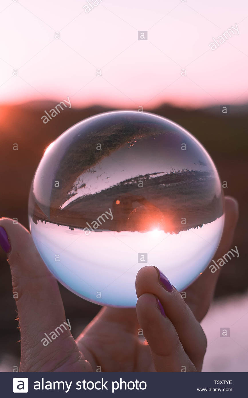 inverted view of field and sunrise through a glass sphere - Stock Image
