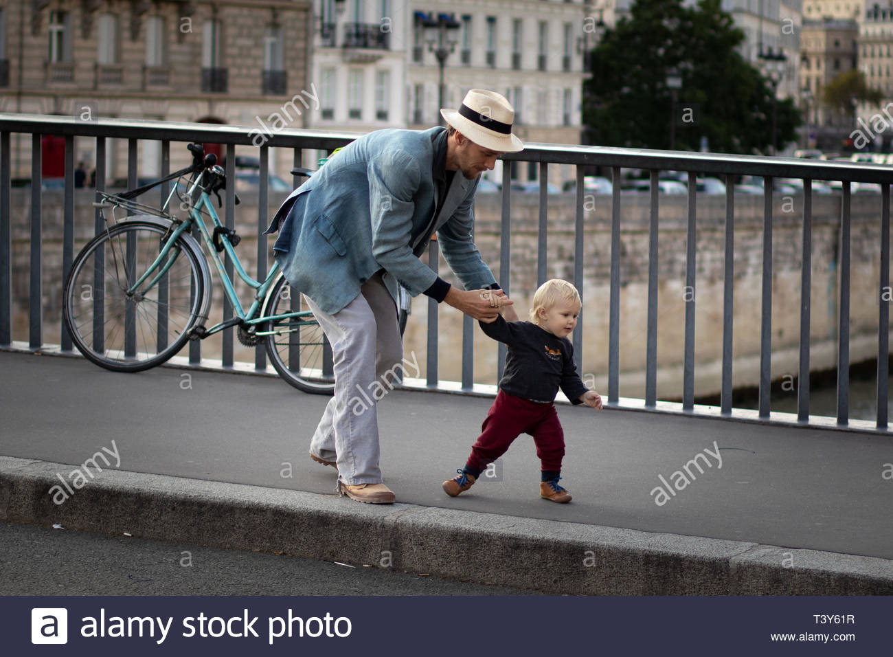 A manwith a hat holds the hand of his baby who begins to walk on the Pont Saint-Louis. August 25, 2018, Paris, France. Un homme avec un chapeau tient  - Stock Image