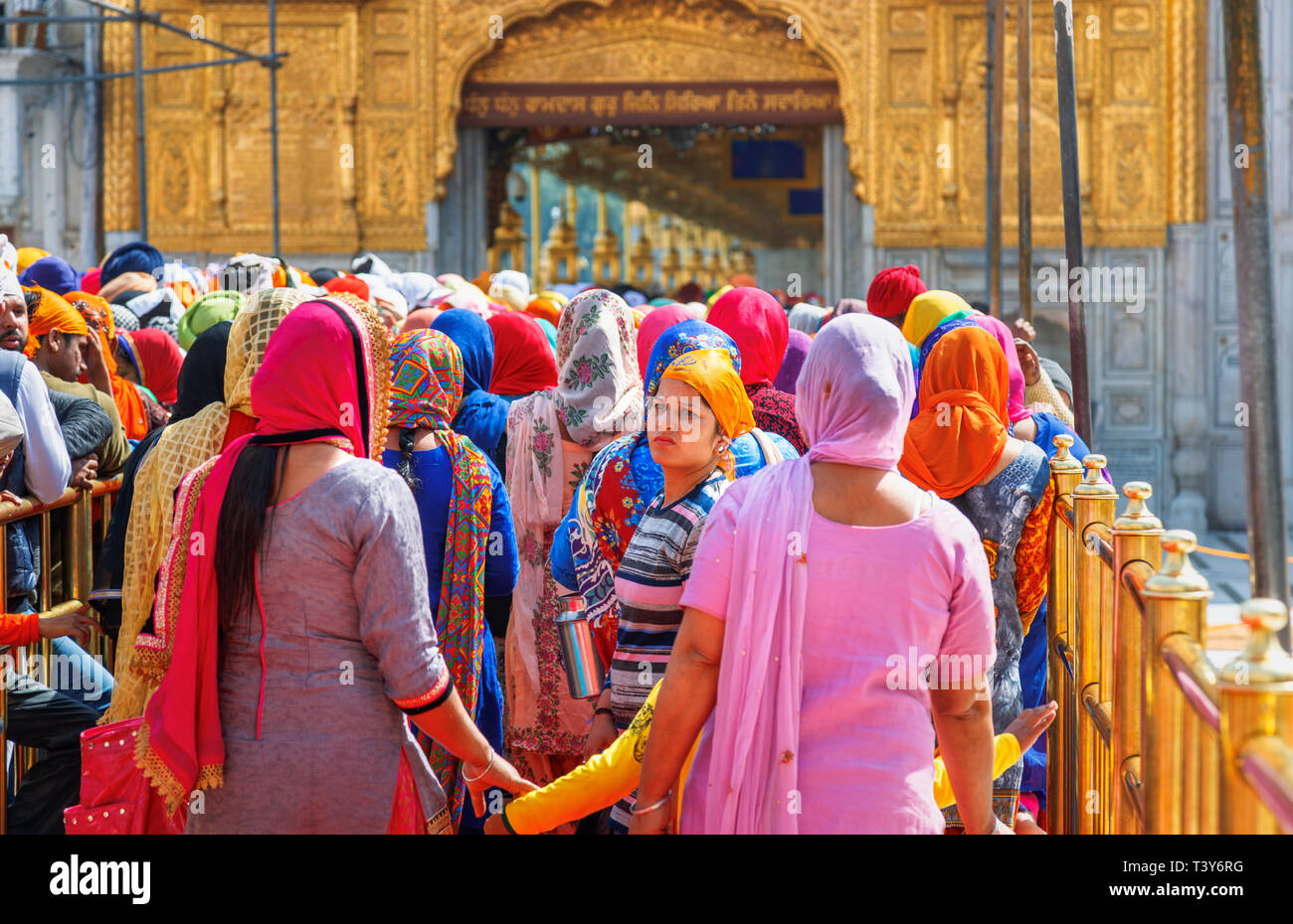 Local Sikhs queuing on the Causeway to enter the Sanctum Sanctorum of the Golden Temple of Amritsar, the holiest pilgrimage site of Sikhism - Stock Image