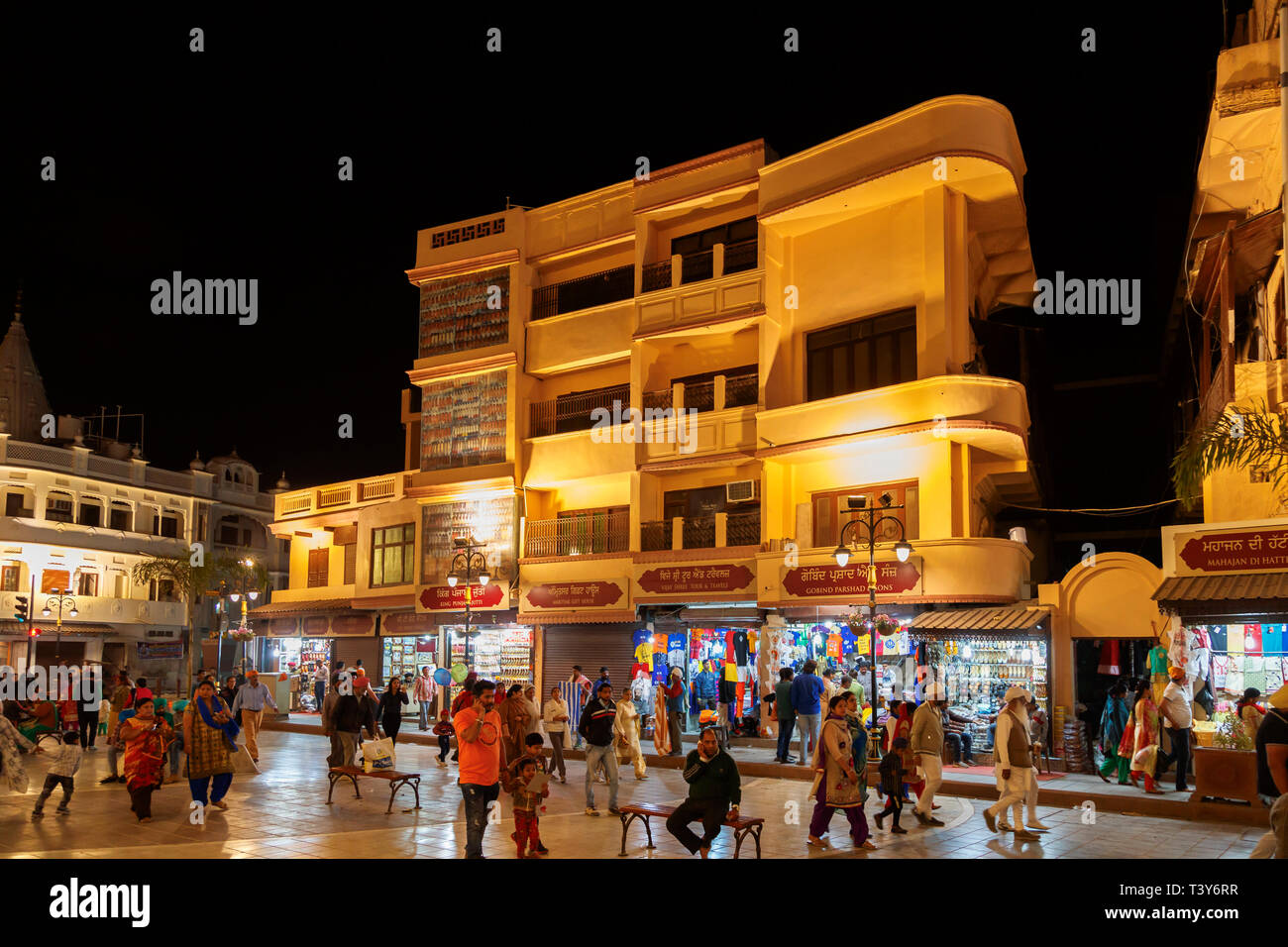 Local people out at night enjoying the bustling pedestrianised shopping area of downtown Amritsar town centre in the evening, Punjab, India - Stock Image