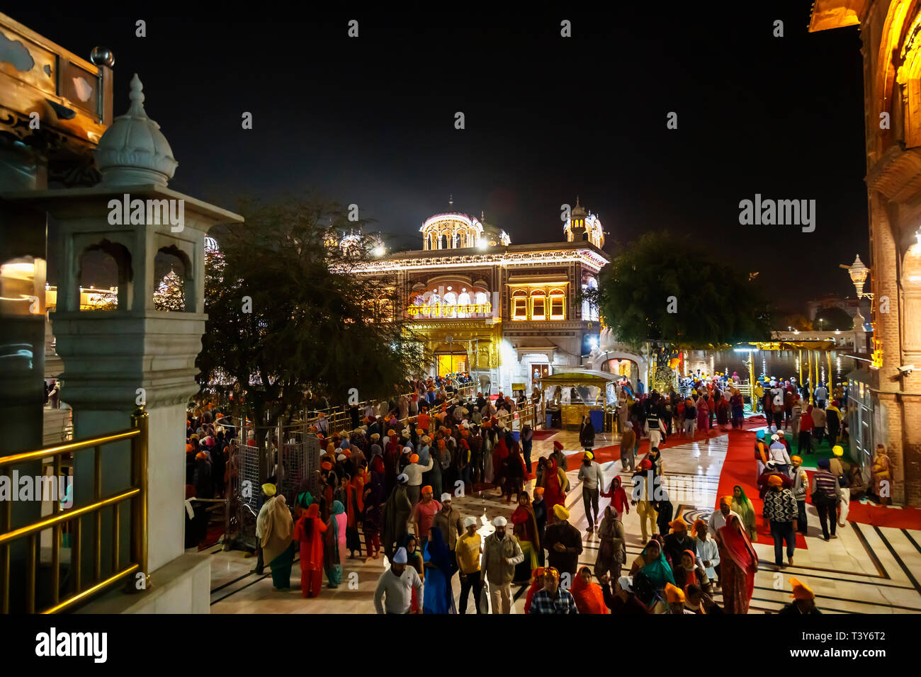 Local Sikhs queueing on the Causeway to enter the Sanctum Sanctorum of the Golden Temple of Amritsar, the holiest pilgrimage site of Sikhism, Punjab - Stock Image
