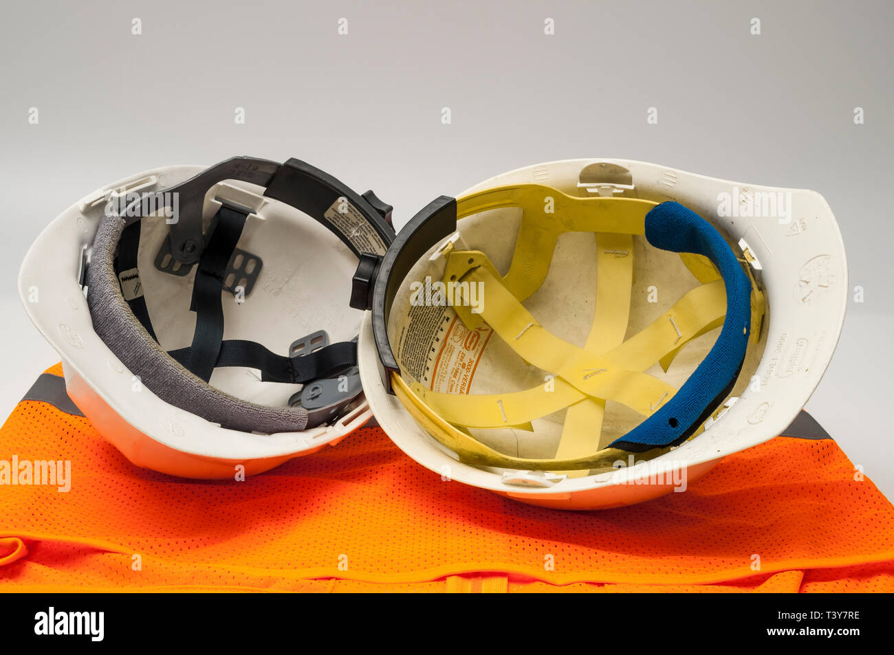 Two old worn hard hats and an orange vest showing inner webbing. - Stock Image