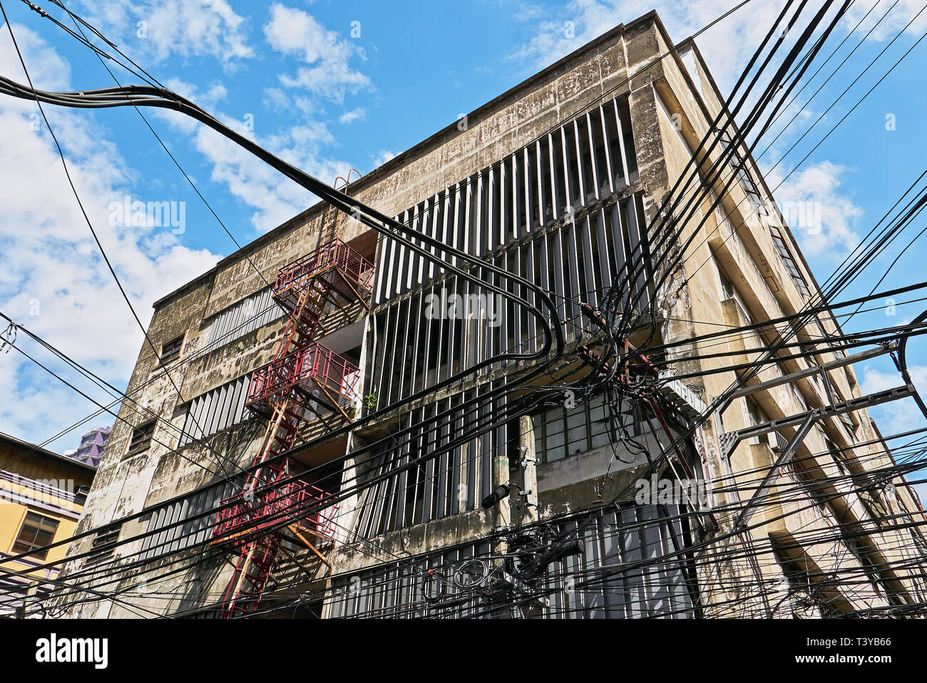 Low-angle view of an old high-rise business building and a mess of cables and power lines in mainly chinese Binondo district, Manila, Philippines - Stock Image