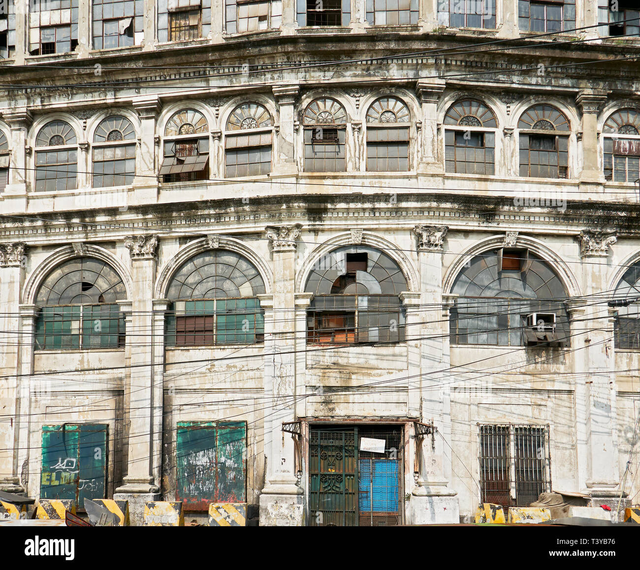 Facade of an old abandoned spanish trade building with power lines in front, in Escolta, Binondo, near the Pasig River, Manila, Philippines Stock Photo